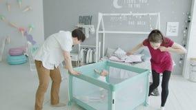 Leuke baby die in box opstaan die ouders bekijken stock footage