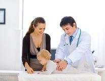 Leuke baby die door een pediatrische arts wordt gecontroleerd stock foto's
