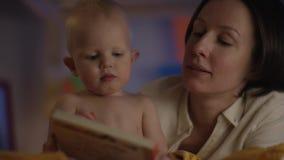 Leuke baby die enkel bij slecht met zijn moeder zitten en zij die een boek voor hem lezen stock videobeelden
