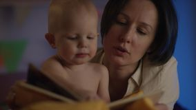 Leuke baby die enkel bij slecht met zijn moeder zitten en zij die een sprookje voor hem lezen stock footage