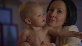 Leuke baby die enkel bij slecht met zijn moeder zitten en zij die hem voeden met candys stock footage