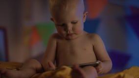 Leuke baby die enkel bij slecht zitten en met de dicht omhoog telefoon spelen stock videobeelden
