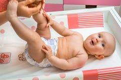 Leuke baby die massage met olie door zijn moeder krijgen Stock Afbeeldingen
