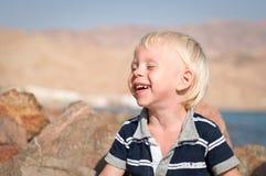 Leuke baby die met gesloten ogen lacht Stock Afbeeldingen