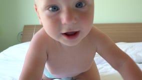 Leuke baby die op bed kruipen stock footage