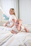 Leuke baby die op bed kruipt terwijl moederhorloges stock afbeeldingen