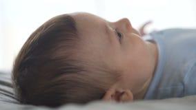 Leuke baby die op het bed liggen, rond kijkend, het glimlachen Zijaanzicht, close-upschot stock video