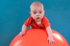 Leuke baby die op oranje fitball op de blauwe achtergrond liggen Co Royalty-vrije Stock Foto's