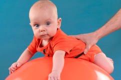 Leuke baby die op oranje fitball op de blauwe achtergrond liggen Co Royalty-vrije Stock Afbeeldingen