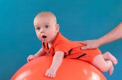 Leuke baby die op oranje fitball op de blauwe achtergrond liggen Co Stock Afbeelding