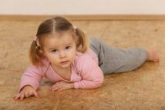 Leuke baby die op vloer liggen stock afbeelding
