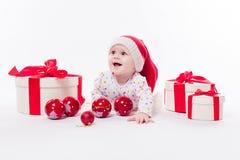 Leuke baby die op zijn maag in een Nieuwjaar ` s GLB liggen onder Christm Stock Afbeelding