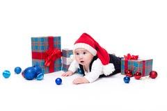 Leuke baby in een rood Nieuwjaar ` s GLB met een glimlach bij zijn gezicht het liggen royalty-vrije stock foto's