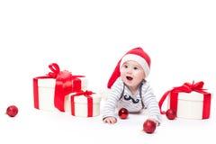 Leuke baby in een rood Nieuwjaar ` s GLB met een glimlach bij zijn gezicht het liggen royalty-vrije stock afbeelding