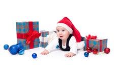 Leuke baby in een rood Nieuwjaar ` s GLB met een glimlach bij zijn gezicht het liggen stock foto's