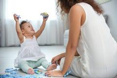 Leuke baby en het jonge moeder spelen royalty-vrije stock fotografie