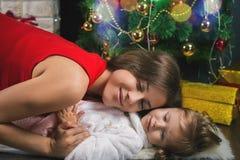Leuke baby en mum het verfraaien van een Kerstboom Rode ballen Stock Foto