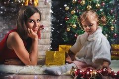 Leuke baby en mum het verfraaien van een Kerstboom Rode ballen Royalty-vrije Stock Foto