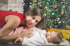 Leuke baby en mum het verfraaien van een Kerstboom Rode ballen Royalty-vrije Stock Afbeeldingen