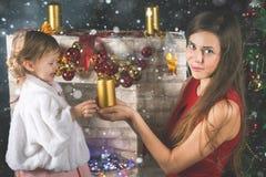 Leuke baby en mum het verfraaien van een Kerstboom Rode ballen Royalty-vrije Stock Foto's