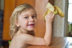 Leuke baby 4 jaar oud het zitten en het eten fruit alleen in keuken Portret van een blonde jongen Het kind glimlacht en eet fruit royalty-vrije stock foto
