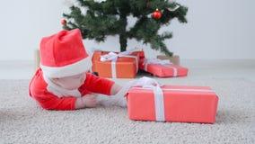 Leuke Baby in kostuum die van Santa Claus, een gift kijken stock video