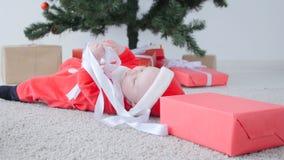 Leuke Baby in kostuum die van Santa Claus, een gift kijken stock footage