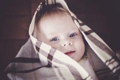 Leuke baby met blauwe ogen die in een het geruite sprei en glimlachen verbergen royalty-vrije stock foto
