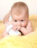 Leuke baby met fles melk op bont Stock Afbeelding