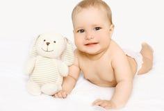 Leuke baby met stuk speelgoed die op het bed liggen Stock Fotografie