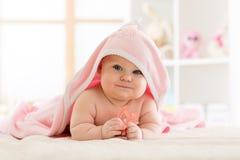 Leuke baby met teether onder een handdoek met een kap na bad stock foto