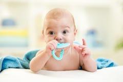 Leuke baby met teetherstuk speelgoed na het baden stock fotografie
