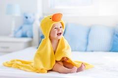 Leuke baby na bad in gele eendhanddoek stock afbeeldingen