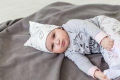 Leuke baby op de grijze deken Ernstig gezicht stock fotografie