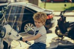 Leuke baby op een motorfiets De zomerreis avontuur Vervoer voor reis Weinig bestuurder Groot jongensconcept gelukkig royalty-vrije stock foto