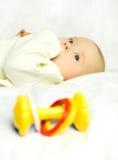 Leuke baby op het bed met een stuk speelgoed Stock Foto's