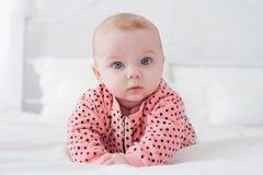 Leuke baby op het witte bed Stock Foto