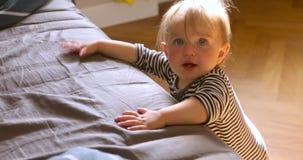 Leuke baby status die op bed leunen stock video