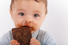 Leuke babyjongen die chocolade eten Royalty-vrije Stock Afbeeldingen