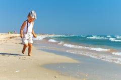 Leuke babyjongen die het overzeese strand in werking stelt Stock Foto's