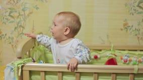 Leuke babyjongen die zich in voederbak bevinden stock footage