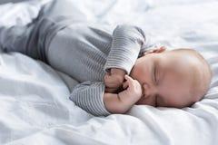 leuke babyjongen in grijze kleren die op wit slapen royalty-vrije stock foto