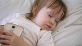 Leuke babyslaap in bed met smartphone Het kind ligt op het hoofdkussen en houdt een tablet stock videobeelden