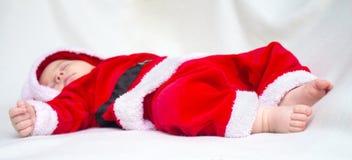 Leuke babyslaap in het rode en witte kostuum van de Kerstmiskerstman Royalty-vrije Stock Fotografie