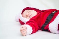 Leuke babyslaap in het rode en witte kostuum van de Kerstmiskerstman royalty-vrije stock afbeelding