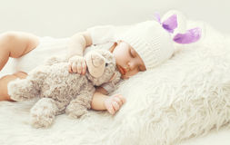 Leuke babyslaap met teddybeerstuk speelgoed op wit zacht bedhuis Royalty-vrije Stock Foto's