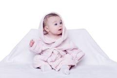 Leuke babyzitting op een stoel in een roze badjas Royalty-vrije Stock Afbeeldingen
