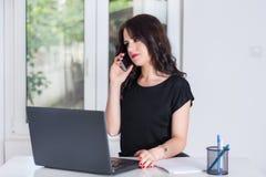Leuke bedrijfsvrouw op kantoor die op de mobiele telefoon spreken en aan laptop werken stock foto