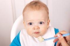 Leuke blauw-eyed babyjongen die havermoutpap eten één jaar die sonMother haar aanbiddelijke jaarzoon voeden royalty-vrije stock foto's
