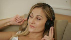 Leuke blond-haired vrouw die aan haar laptop werken terwijl het luisteren aan muziek stock videobeelden